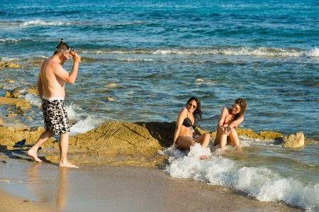 molest: Typically persistent guy harassing sunbathing girls on the beach Stock Photo