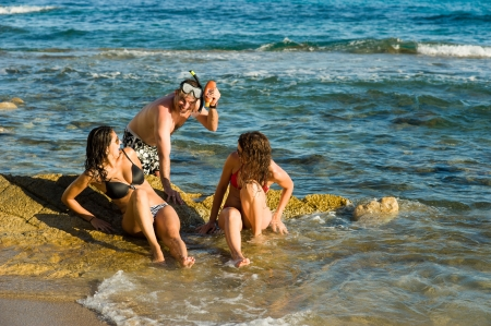 harassing: Typically persistent guy harassing sunbathing girls on the beach Stock Photo