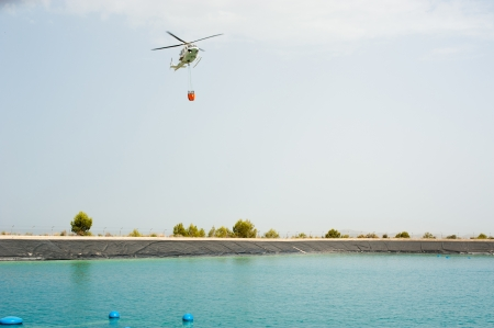 Approach of a firefighter helicopter to fill up its water bucket photo