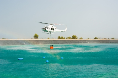 Helicopter dipping its bucket to load water photo