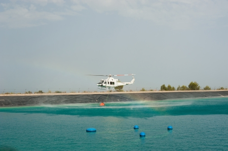 Firefighter helicopter loading water while extiguising a forest fire photo