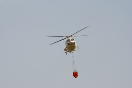Firefighter helicopter in flight while on a fire extinguishing mission photo