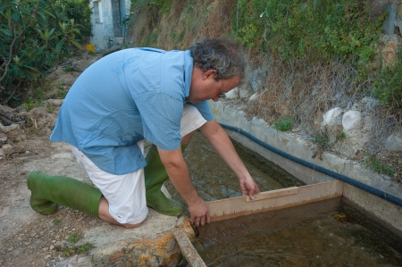 Farmer at a traditional irrigation ditch redirecting water photo