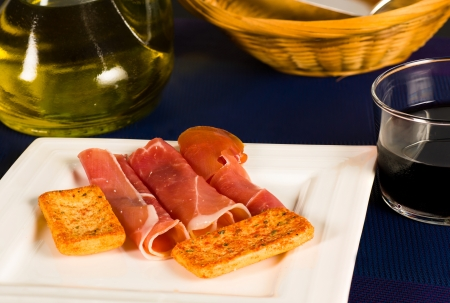 Slices of Spanish serrano ham with red wine and olive oil in the background photo
