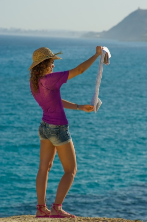 Woman checking out a map against the backround of a sunny Mediterranean coast Stock Photo - 14544562