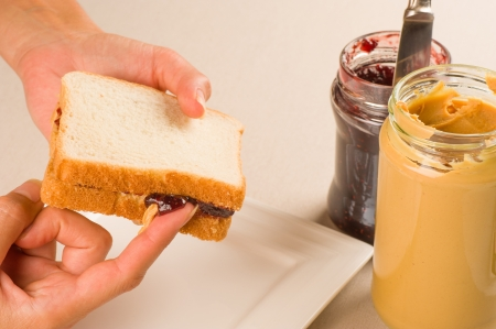 Dripping raspberry jam and peanut butter sandwich photo