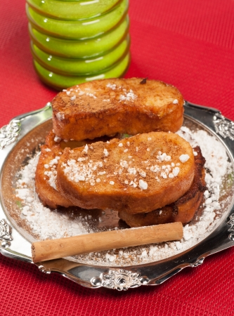cinammon: A portion of traditional  Spanish torrijas, sweet fried bread slices scented with cinammon