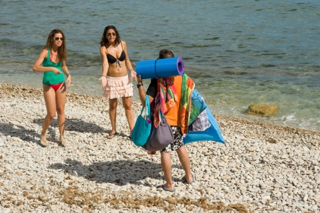 Poor guy completely overloaded with the girl´s beach stuff photo