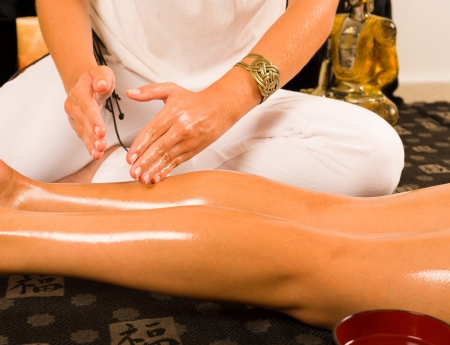 Hands massaging thighs in an oriental setting photo