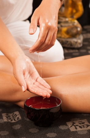 Massage therapist moistening her hands in oil photo