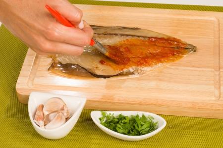 Preparing a mackerel in marinade, a Mediterranean recipe photo