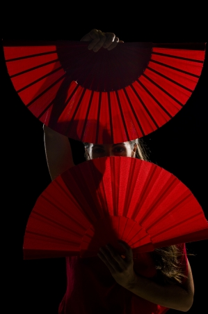 Flamenco dancer hiding behind her open folding fans photo