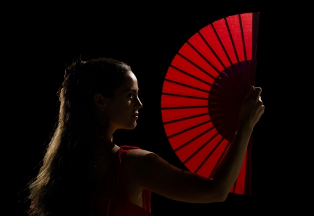 Female dancer holding a backlit red folding fan photo