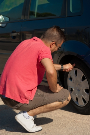 motorist: Male motorist checking the state of his tyres Stock Photo