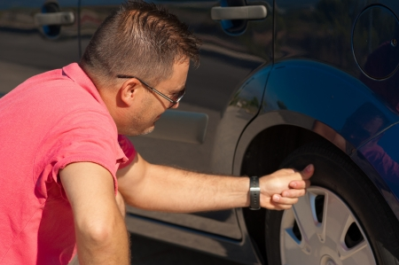 motorist: Male motorist checking the condition of a tyre