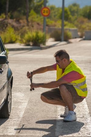 helpless: Looking quite helpless with his car repair effort Stock Photo