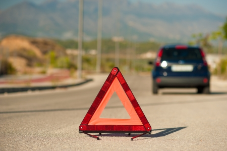 Broken down car marked by a red warning triangle photo