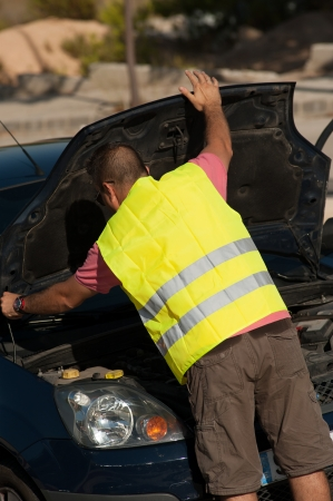 reflective vest: Reflective vest on and opening the car bonnet