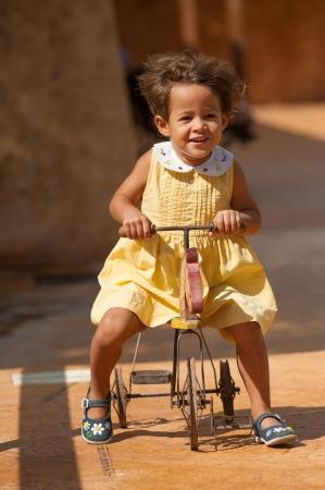 centenarian: Muchacha feliz que monta un triciclo de juguete centenario