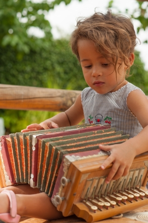 Cute girl playing with a vintage accordion photo