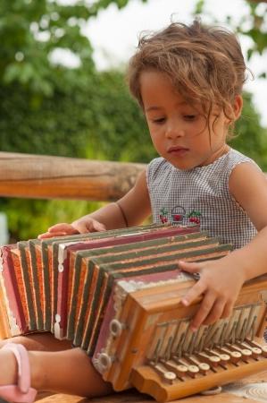 acordeon: Linda chica jugando con un acorde�n vendimia Foto de archivo