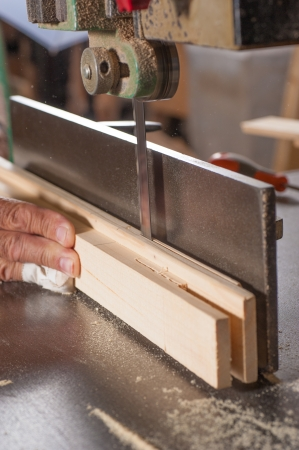 Workplace risks: carpenter working on a sawing table with a bandaged finger Stockfoto