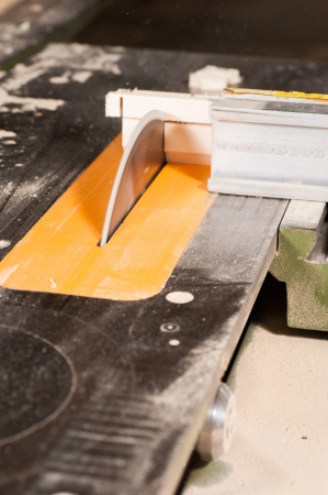 Circular table saw in action in a carpenter workshop photo