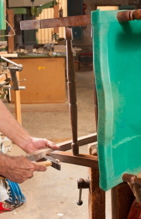 restoring: Carpenter hands working at restoring an old chair Stock Photo