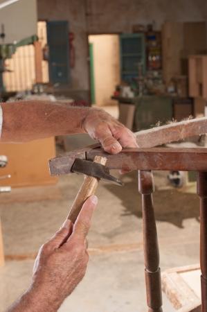herramientas de carpinteria: Manos con martillo trabajando en una vieja silla