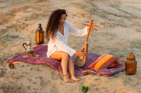 Woman with a sitar in a desert  setting photo