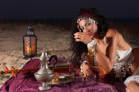 Attractive brunette drinking Moroccan tea in a desert setting photo