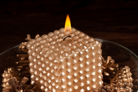 Burning golden candle surrounded by fir cones Stock Photo - 15882187