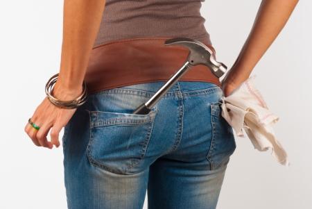 A hammer in a femal jeans pocket, a concept Reklamní fotografie