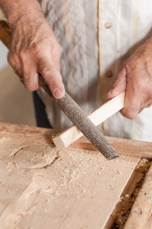 rasp: Carpenter working with a traditional rasp tool