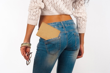 tight fitting: Old book in a tight fitting sexy jeans pocket Stock Photo