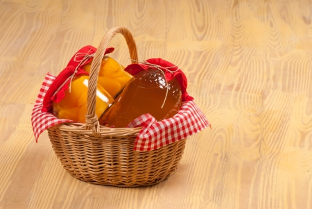 Traditional basket with autumn harvest products in jars photo