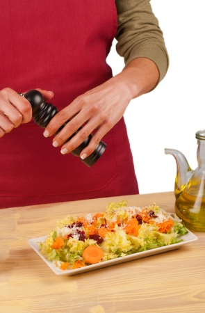 freshly prepared: Grinding pepper on a freshly prepared salad Stock Photo