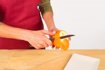 skinning: Female hands peeling a fresh orange Stock Photo