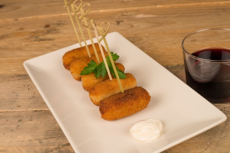 Freshly fried croquettes on a wooden table photo