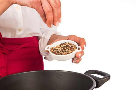 Seasoning a stew with fresh pepper grains Stock Photo - 18499313