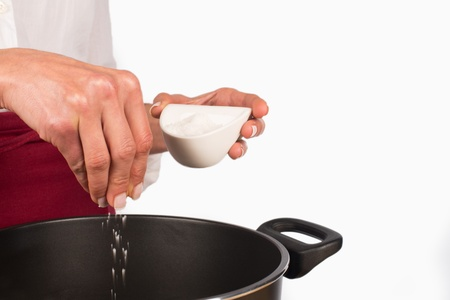 put: Female hands salting the content of a stewing pot