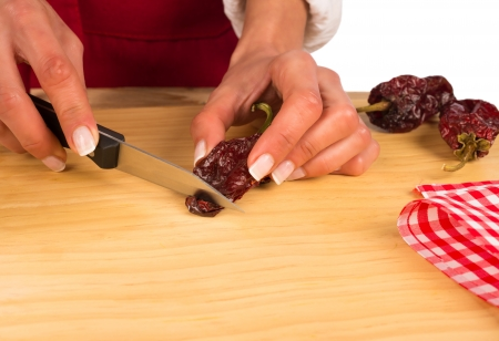 Hot peppers being chopped on a kitchen board Stock Photo