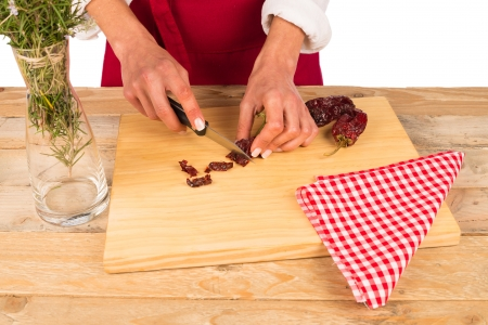 ingedient: Hot peppers being chopped on a kitchen board Stock Photo