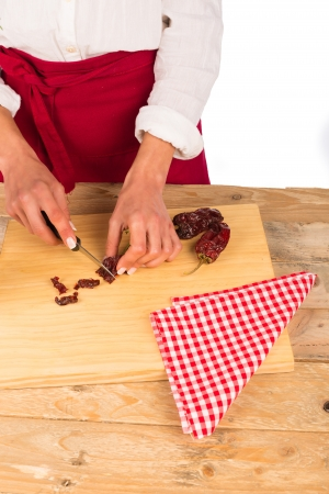 ingedient: Female hand chopping dried peppers on a kitchen board