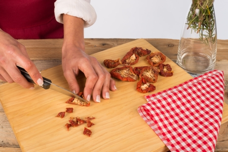 ingedient: Female hands chopping sundried Italian tomatoes Stock Photo