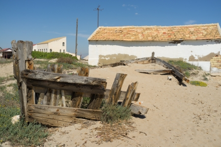 ashore: Wreckage of a traditional salt mine boat ashore on a sandy beach