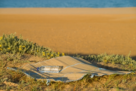 beach mat: A beach mat sitting on top of  a dune on a sunny beach day Stock Photo
