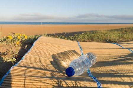 beach mat: A bottle of fresh mineral water on a beach mat, a summertime concept Stock Photo