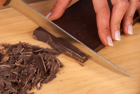 obtain: Female hands using a knife to obtain fine black chocolate shavings