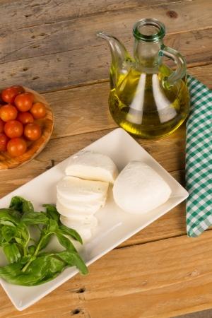 Freshly chopped mozzarella surrounded by salad ingredients photo